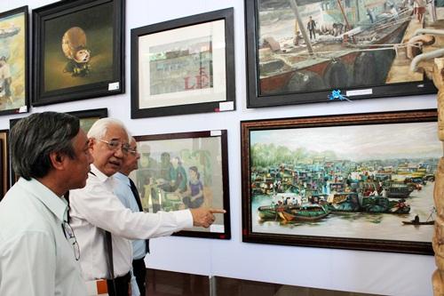 Họa sĩ Trần Khánh Chương (người ở giữa) - Chủ tịch Hội Mỹ thuật Việt Nam thuyết trình về các tác phẩm tham gia triển lãm với lãnh đạo tỉnh Tiền Giang
