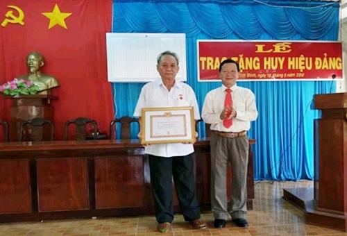 Đồng chí Huỳnh Hữu Thành, TUV, Bí thư Huyện ủy Gò Công Tây trao Huy hiệu 50 năm cho đồng chí Nguyễn Văn Nghễ tại Đảng bộ thị trấn Vĩnh Bình