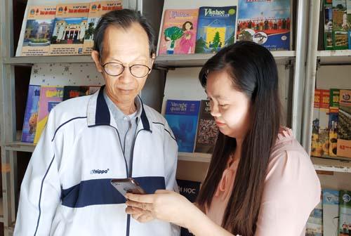 Nhân viên Thư viện tỉnh hướng dẫn độc giả sử dụng sách điện tử